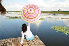 在一艘竹木筏的妇女伞 免版税图库摄影