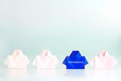 在一蓝色的区别词在白色origami衬衣纸,联合国中 免版税库存照片