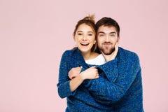 在一蓝色的年轻美好的夫妇编织了摆在微笑的毛线衣获得在浅粉红色的背景的乐趣 免版税库存照片