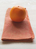 在一被烧的桔黄色餐巾placemat的橙色果子 库存照片