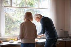 在一起准备早餐的中年夫妇的背面图  免版税库存照片