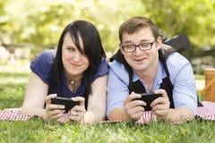 在一起发短信的公园的年轻夫妇 免版税库存图片