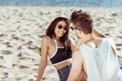 在一起坐和微笑对沙滩的太阳镜的年轻夫妇 免版税库存照片