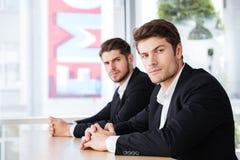 在一起坐在办公室的衣服的两个确信的商人 免版税库存照片