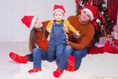 在一起坐在装饰的树附近的圣诞前夕的愉快的家庭 库存照片