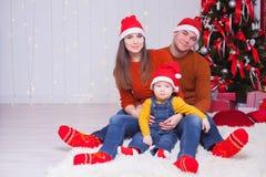 在一起坐在装饰的树附近的圣诞前夕的愉快的家庭 图库摄影