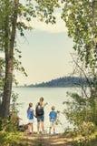 在一起天高涨的家庭在一个美丽的山湖附近 库存图片