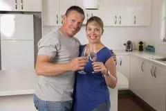 在一起庆祝周年或情人节用香槟或酒的爱的年轻美好的夫妇30s或40s在家敬酒 免版税库存图片