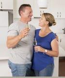 在一起庆祝周年或情人节用香槟或酒的爱的年轻美好的夫妇30s或40s在家敬酒 免版税库存照片