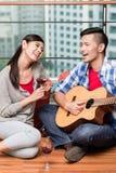 在一起搬以后年轻人演奏他的girlfrie的爱情歌曲 免版税图库摄影