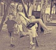 在一起摇摆在儿童` s操场的孩子的看法 库存图片