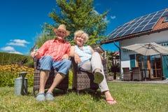 在一起放松在a的庭院里的爱的愉快的资深夫妇 库存照片