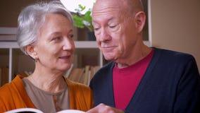 在一起是电视的看书的资深白种人夫妇殷勤和对图书馆感兴趣 影视素材