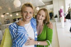 在一起服装店画象的年轻夫妇购物 库存照片