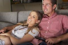 在一起看电视的沙发的夫妇 免版税库存图片