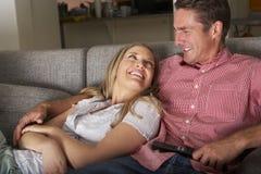 在一起看电视的沙发的夫妇 图库摄影