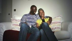 在一起看电视的沙发的成熟非裔美国人的夫妇 股票录像