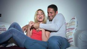在一起看电视的沙发的年轻夫妇 影视素材