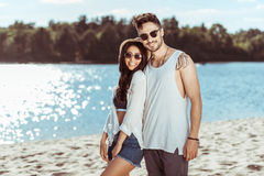 在一起站立和微笑对照相机的太阳镜的年轻夫妇对沙滩 免版税库存图片