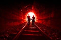 在一起走在一条铁路隧道的爱的夫妇 免版税库存照片