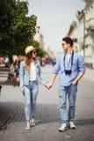 在一起走在街道上的爱的美好的旅游夫妇 愉快的年轻人和微笑的妇女走在老镇街道附近的, Lo 免版税库存照片