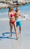 在一起走的泳装的快乐的夫妇 库存图片
