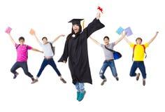 在一起跳跃毕业生的长袍的愉快的小组 库存图片