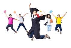 在一起跳跃毕业生的长袍的愉快的小组 免版税库存图片