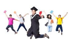 在一起跳跃毕业生的长袍的愉快的小组 免版税库存照片