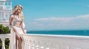 在一身庄重装束的美好,性感的白肤金发的模型在圣托里尼 免版税库存图片