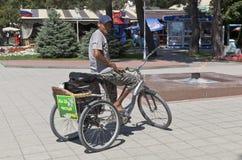 在一辆三轮车的道路清扫工有名字标志的我们是为干净的城市!在堤防Gelendzhik 库存图片