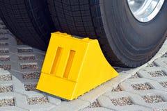 在一辆停放的卡车的轮子的黄色塞子 免版税库存图片