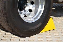 在一辆停放的卡车的轮子的黄色塞子 免版税图库摄影