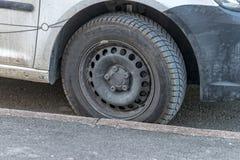 在一辆停放的汽车的破旧的冬天车胎 免版税库存照片