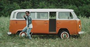 在一辆减速火箭的搬运车前面的精力充沛的年轻人跳舞,在自然中间 股票录像