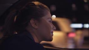 在一辆出租汽车的愉快的美好的女孩骑马在坐后座和看从窗口的晚上夜城市 股票视频