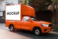 在一辆卡车的空白的白色标志给的大厦后面做广告 库存图片