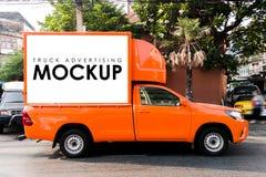 在一辆卡车的空白的白色标志给的大厦后面做广告 图库摄影