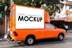在一辆卡车的空白的白色标志给的大厦后面做广告 免版税图库摄影