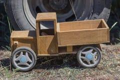 在一辆大卡车的轮子的背景的木玩具卡车 免版税库存照片