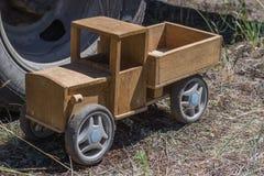 在一辆大卡车的轮子的背景的木玩具卡车 图库摄影