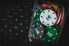 在一辆小台车的纸牌筹码在键盘膝上型计算机 在互联网上的赌博的瘾 图库摄影