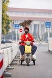在一辆小电三轮车的滑稽的道路清扫工,北京,中国 免版税库存图片