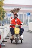 在一辆小电三轮车的滑稽的道路清扫工,北京,中国 库存图片