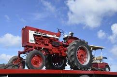 在一辆平板车拖车被拖拉的Farmall 806拖拉机 图库摄影