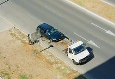 在一辆拖车的装载的打破的汽车在路旁 免版税库存照片