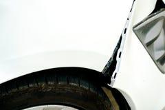 在一辆损坏的白色汽车的消弱的和开头创伤 免版税库存照片