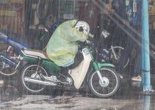 在一辆摩托车的一位出租汽车司机在雨 库存图片