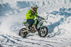 在一辆摩托车的小辈车手在雪道种族 库存照片