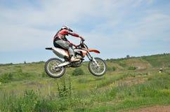 在一辆摩托车的摩托车越野赛车手在上涨 库存照片